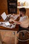 Homme handicapé notant tout en utilisant un ordinateur portable à la maison — Photo de stock