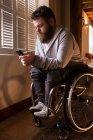 Handicapés utilisant un téléphone portable à la maison — Photo de stock
