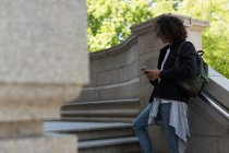 Young man using mobile phone outside library building — Stock Photo
