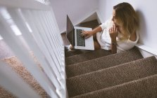 Mujer usando el ordenador portátil mientras está sentado en la escalera en casa - foto de stock