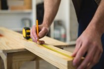 Mid section of male carpenter measuring and marking wood in workshop — Stock Photo