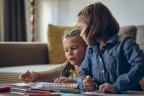 Siblings studying together in living room at home — Stock Photo