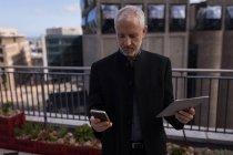 Uomo d'affari utilizzando la telefonia mobile e tablet digitali nei locali dell'hotel — Foto stock