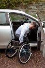Uomo giovane disabile su sedia a rotelle imbarco nella sua auto — Foto stock