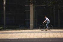 Bicicletta di guida uomo sul marciapiede in città — Foto stock