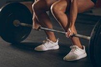 Крупный план крепкой женщины, поднимающей штангу в спортзале — стоковое фото