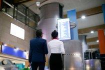 Homme d'affaires et femme regardant Conseil de départ à l'aéroport — Photo de stock