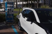 Electric car being charged at charging station on a sunny day — Stock Photo