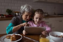 Grandmother and granddaughter using digital tablet in kitchen at home — Stock Photo