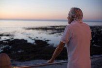 Задумчивый пожилой человек, стоящий возле пляжа в сумерках — стоковое фото