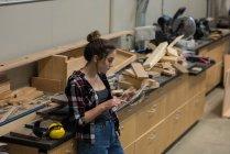 Женский плотника, с использованием цифрового планшета на семинаре — стоковое фото