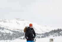 Мужчины альпинист, держась теперь охватывает горные лыжные палки в зимний период — стоковое фото