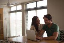 Couple heureux en utilisant un ordinateur portable à la maison — Photo de stock