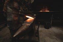 Schmied Prüfung einen heißem Metall Stab in Werkstatt — Stockfoto