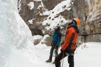 Пара стоя вместе вблизи скалистых гор в зимний период — стоковое фото