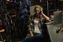 Женщины механик, говоря на мобильном телефоне в мастерской — стоковое фото