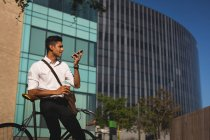 Businessman talking on mobile phone outside office premises on a sunny day — Stock Photo