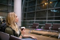 Woman having coffee while waiting in waiting area at airport terminal — Stock Photo