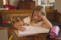 Очаровательная девушка делает домашнее задание дома — стоковое фото