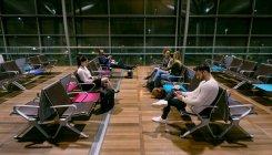 Viajeros esperando en sala de espera en el aeropuerto - foto de stock