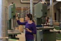 Female carpenter using digital tablet at workshop — Stock Photo