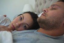 Pareja durmiendo en la cama en el dormitorio en casa - foto de stock
