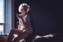 Donna che per mezzo del telefono mobile nel soggiorno a casa — Foto stock