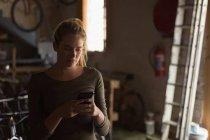 Молода жінка механік за допомогою мобільного телефону в майстерні — стокове фото