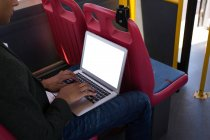 Mid section of businessman using laptop while travelling in bus — Stock Photo