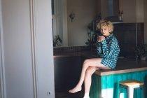 Jovem mulher tendo na cozinha em casa — Fotografia de Stock