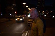 Homme âgé qui attend dans la rue de la ville la nuit — Photo de stock