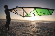 Surfista maschio che tiene un aquilone sulla spiaggia al crepuscolo — Foto stock