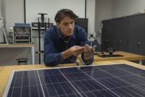 Male worker working on solar panel in office — Stock Photo