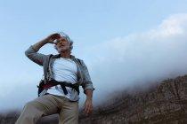 Caminhante sênior protegendo os olhos em uma montanha — Fotografia de Stock