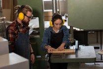 Menuisiers et menuisières travaillant ensemble sur une machine de coupe verticale en atelier — Photo de stock