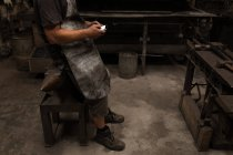 Blacksmith using mobile phone in workshop — Stock Photo