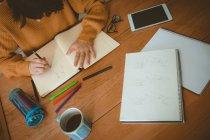 Frau eine Skizze in einem Buch zu Hause — Stockfoto