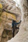 Чоловічий альпініст, стоячи біля Скелясті гори взимку — стокове фото