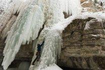 Scalatore di roccia maschile arrampicata montagna di ghiaccio durante l'inverno — Foto stock