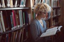 Giovane donna che legge un libro in biblioteca — Foto stock