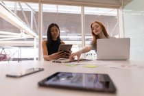 Female executives using digital tablet and laptop at desk in office — Stock Photo