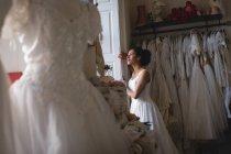 Femme métisse, mariée en robe blanche regardant par la fenêtre à la boutique — Photo de stock