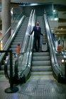 Uomo d'affari in piedi sulla scala mobile con i bagagli all'aeroporto — Foto stock