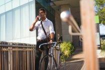 Empresario hablando por teléfono móvil mientras camina con su bicicleta en las instalaciones de oficina - foto de stock