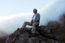 Caminhante sênior sentado em uma rocha no campo — Fotografia de Stock