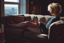 Woman reading a book in living room at home — Stock Photo
