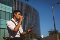 Young businessman using mobile phone at office premises — Stock Photo