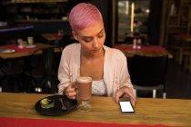 Femme élégante à l'aide de téléphone portable tout en ayant le milkshake au chocolat au restaurant — Photo de stock