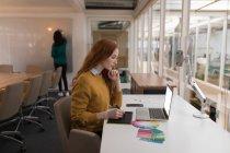 Diseñadora gráfica femenina usando tableta gráfica en la oficina - foto de stock