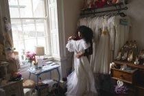 Afrikanerin Kleiderbügel in der Boutique Brautkleid auswählen — Stockfoto